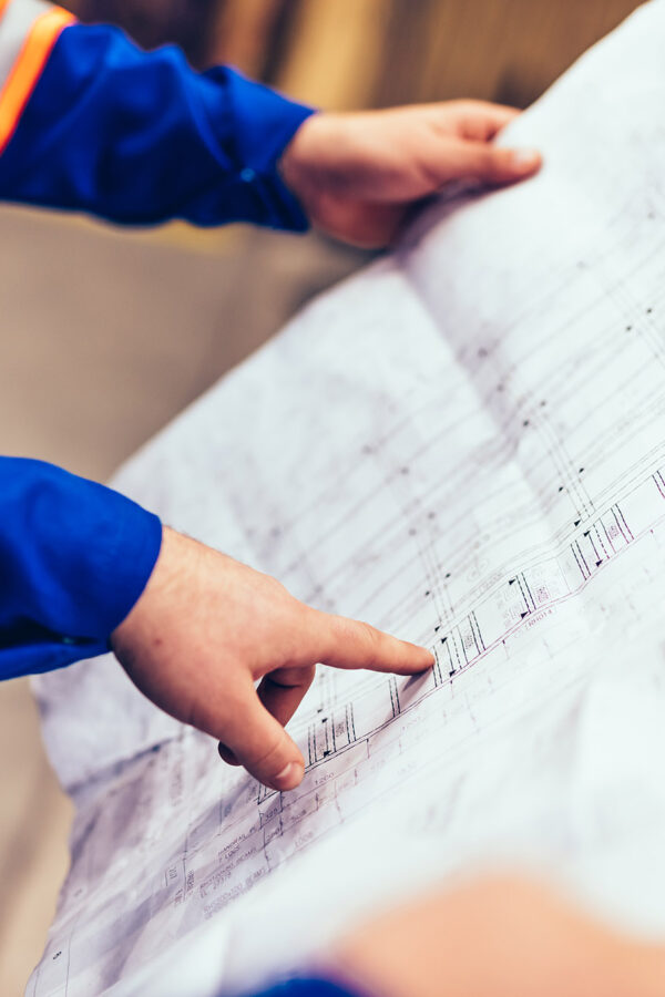 Engineers showing construction plans in a factory. Heavy industry